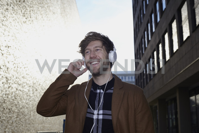 Smiling young man listening music with headphones at backlight - FMKF002246 - Jo Kirchherr/Westend61