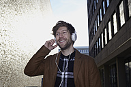Smiling young man listening music with headphones at backlight - FMKF002246