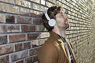 Young man leaning against brick wall listening music with headphones - FMKF002249