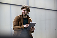Portrait of smiling young man with digital tablet - FMKF002258