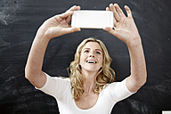Portrait of smiling young woman taking a selfie with smartphone in front of chalkboard - FMKF002267