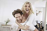 Portrait of happy couple having fun at home - FMKF002270