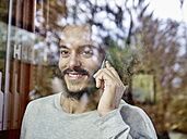 Smiling young man on cell phone behind windowpane - RHF001224