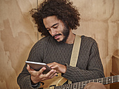 Young man with electric guitar looking at digital tablet - RHF001233