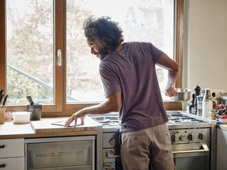 Young man standing at stove in kitchen checking digital tablet - RHF001248