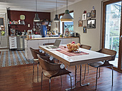 Laptop on dining table in open plan kitchen with man in background - RHF001251