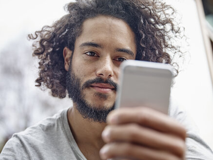 Young man looking at cell phone - RHF001263