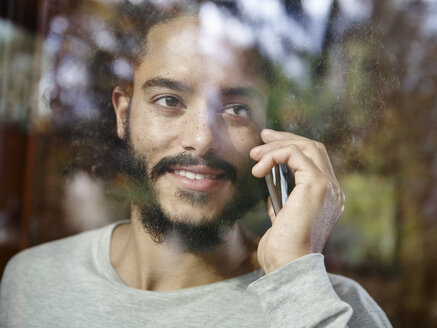 Smiling young man on cell phone behind windowpane - RHF001266