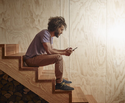 Young man sitting on wooden stairs looking at digital tablet - RHF001269