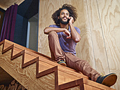 Young man on wooden stairs talking on cell phone - RHF001272