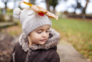 Portrait of little girl with autumn leaf on her wooly hat - MGOF001246