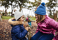 Two talking girls on a playground in autumn - MGOF001252