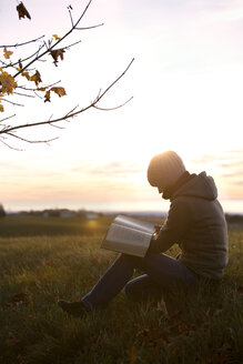 Germany, woman reading a book on an autumnal meadow at sunrise - MIDF000712