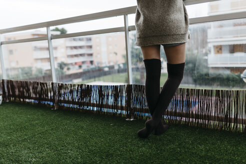 Woman wearing overknees standing on balcony, partial view - JRFF000307
