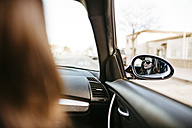 Female front passanger in car reflected in car mirror - JRFF000315