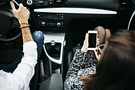 Young couple driving in a car, co driver using smart phone - JRFF000324