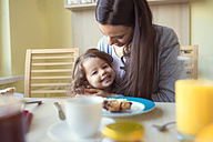Portrait of smiling little girl and her mother at breakfast table - HAPF000115