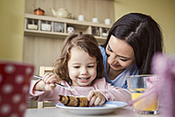 Portrait of little girl and her mother at breakfast table - HAPF000127