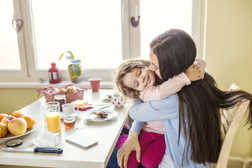 Portrait of smiling little girl hugging her mother at breakfast table - HAPF000130