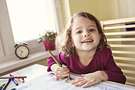 Portrait of smiling little girl painting with coloured pencils - HAPF000136
