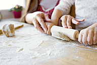 Mother helping her little daughter rolling out dough, close-up - HAPF000139