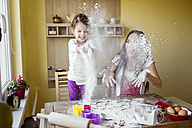 Mother and her little daughter throwing flour in the air at the kitchen - HAPF000157