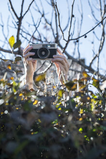 Woman's hands shooting pictures over a hedge with an old camera - DEGF000603