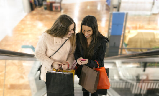Two female friends with shopping bags on an escalator of a shopping center looking at smartphone - MGOF001264