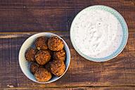 Preparation of falafel, vegetan falafel patties, joghurt in bowl - SARF002453