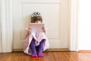 Little girl dressed up as a princess looking at digital tablet - LVF004416
