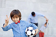 Boy holding soccer ball and making victory sign, family playing in background - VABF000048