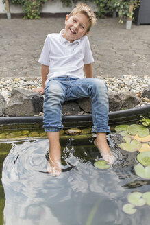 Portrait of little boy refreshing his feet in a lily pond - PAF001536