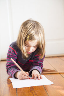 Little girl lying on the floor drawing something - LVF004421