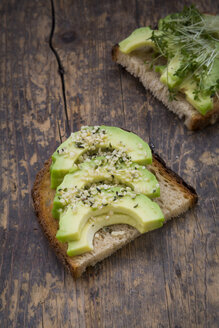 Slice of toasted bread with acocado, cress and hemp seeds on wood - LVF004425