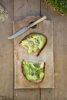 Slice of toasted bread with acocado, cress and hemp seeds on wooden board - LVF004434