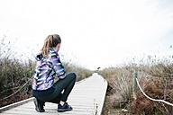 Spain, Tarragona. Woman ready to start running on a wooden footbridge - JRFF000334