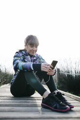 Young woman relaxing after running, using smartphone - JRFF000337