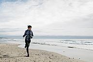 Spain, Tarragona, Woman running on a beach in winter - JRFF000340