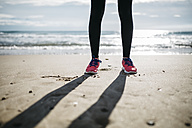 Legs and sneakers on the sand of a beach - JRFF000343