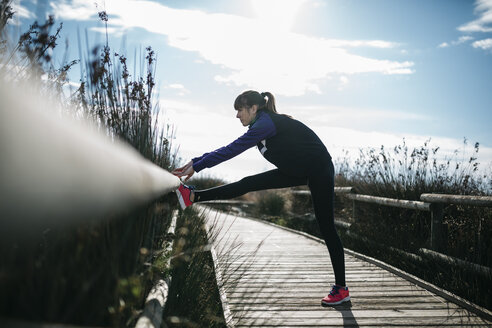 Spain, Tarragona, Woman doing stretching before running - JRFF000346