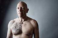 Portrait of bald man with tattoo on chest and arms - JATF000816