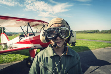 Germany, Dierdorf, Boy in front of biplane wearing old pilot outfit - PAF001538