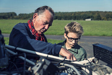 Germany, Dierdorf, Grandfather and grandson repairing biplane - PAF001544