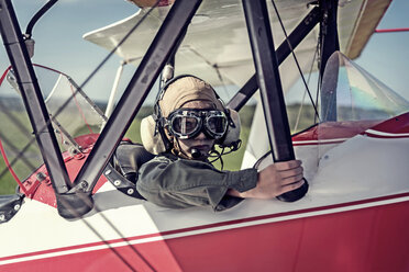 Germany, Dierdorf, Boy sitting in biplane wearing old pilot outfit - PAF001547
