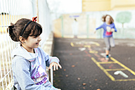 Portrait of smiling little girl playing outside - MGOF001273