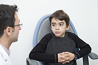 Optometrist talking to boy in chair - ERLF000103