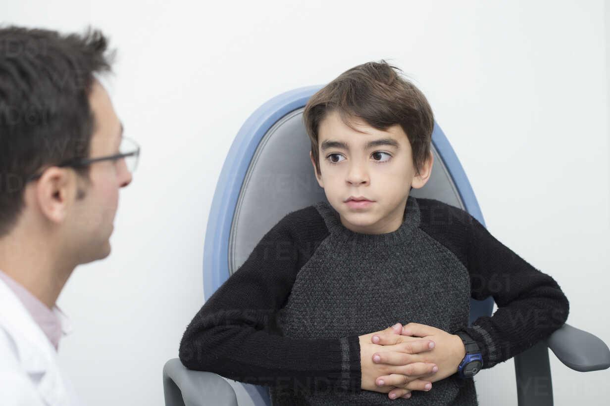 Optometrist talking to boy in chair - ERLF000103 - Enrique Ramos/Westend61