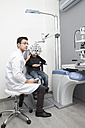 Optometrist examining eyesight of boy - ERLF000109