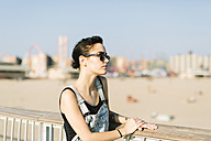 USA, New York, Coney Island, young woman relaxing at beach promenade - GIOF000632