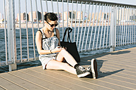 USA, New York, Coney Island, young woman checking the phone on pier - GIOF000635